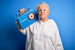 Senior beautiful woman holding vintage radio standing over isolated blue background with a confident expression on smart face thinking serious