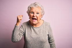 Senior beautiful woman wearing casual t-shirt standing over isolated pink background angry and mad raising fist frustrated and furious while shouting with anger. Rage and aggressive concept.