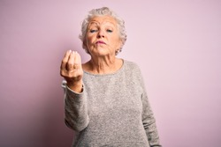 Senior beautiful woman wearing casual t-shirt standing over isolated pink background Doing Italian gesture with hand and fingers confident expression