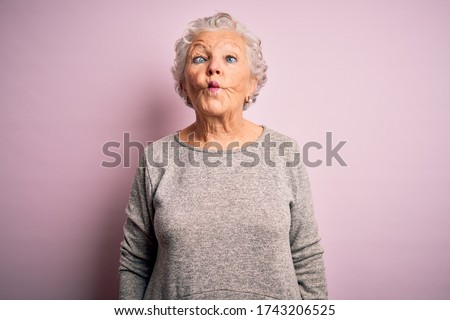 Senior beautiful woman wearing casual t-shirt standing over isolated pink background making fish face with lips, crazy and comical gesture. Funny expression.