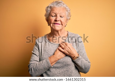 Senior beautiful woman wearing casual t-shirt standing over isolated yellow background smiling with hands on chest with closed eyes and grateful gesture on face. Health concept. ストックフォト ©