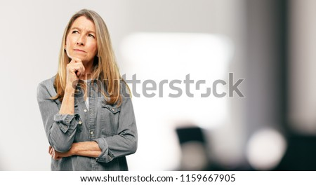 senior beautiful woman With a confused and thoughtful look, looking sideways, thinking and wondering between different options.