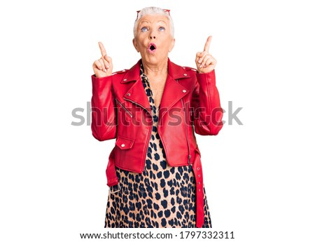 Senior beautiful woman with blue eyes and grey hair wearing a modern style with a red leather jacket amazed and surprised looking up and pointing with fingers and raised arms.