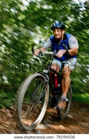 Senior beim radfahren im Wald