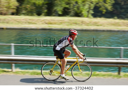 Senior bicyclist on road bike. Blurred background. Copy space