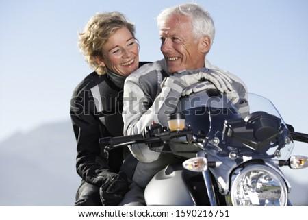 Senior biker couple smiling on motorcycle