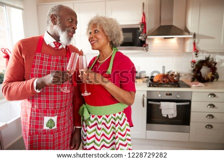 Senior black couple wearing aprons take a break from preparing Christmas dinner to make a toast, close up