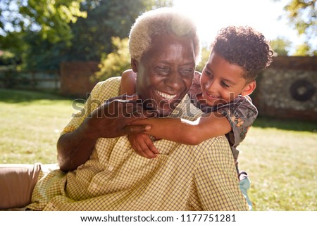 Senior black man sitting on grass, embraced by his grandson