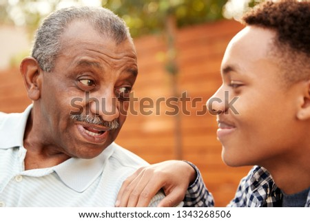 Senior black man talking with his young adult grandson, close up