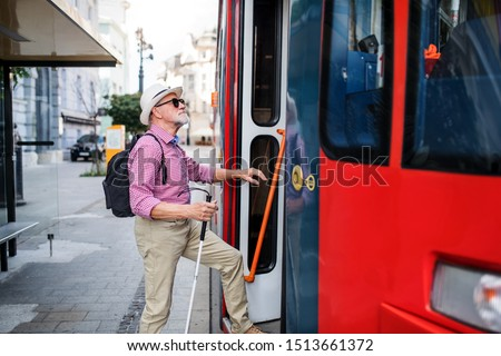Senior blind man with white cane getting on public transport in city. #1513661372