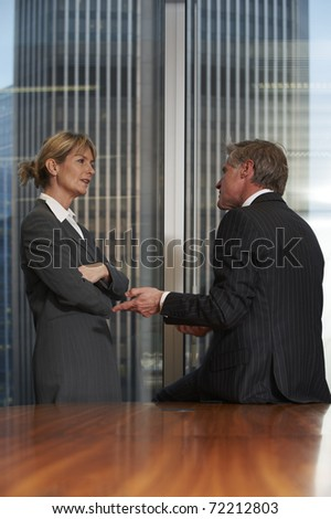 Senior business man and woman in a boardroom having a conversation