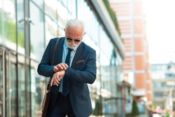 Senior business man looking at wristwatch