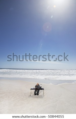Senior business man sitting at office desk on beach, elevated view