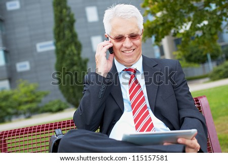 Senior business man working with tablet PC in a park