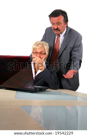 Senior Business People In Front Of Laptop A business woman and a man in front of a laptop on a desk. The man explains something to the woman. The woman is shocked. Isolated over white.