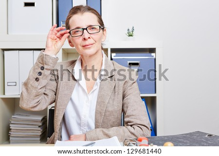 Senior business woman in the office at her desk looking through glasses
