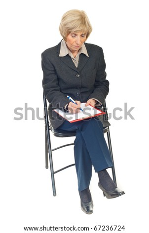 Senior business woman sitting on chair and writing in her folder isolated on white background