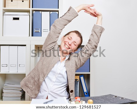 Senior business woman with back pain stretching in her office