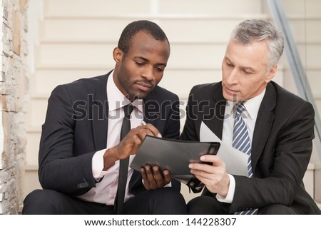 Senior businessman and mid adult businessman working together. They are sitting on staircase and reading a papers