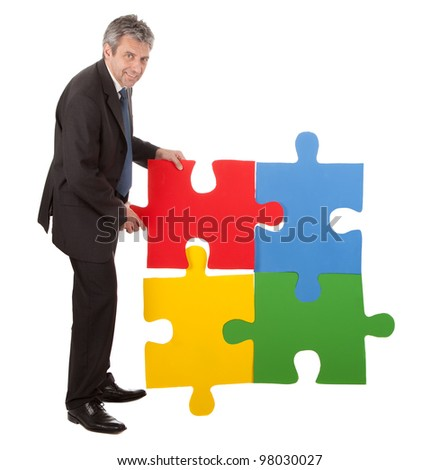 Senior businessman assembling a jigsaw puzzle. Isolated in white