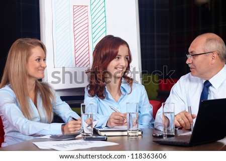 Senior businessman discuss with two young attractive businesswomen, background in the office - Shutterstock ID 118363606