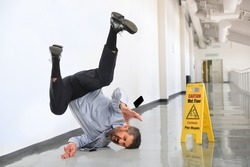 Senior businessman falling on wet floor inside office building