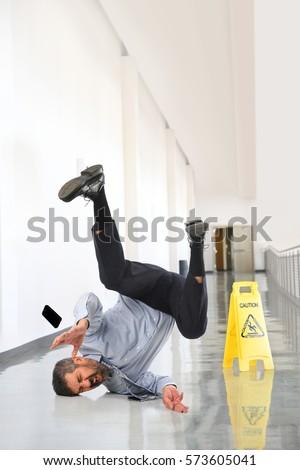 Senior businessman falling on wet floor inside office building #573605041