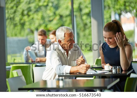 Senior businessman giving consultation to a young woman in a meeting #516673540