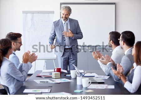 Senior businessman having a speech by a whiteboard during a conference business meeting  in an office. Business concept