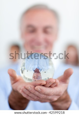 Senior businessman holding a crystal ball at work