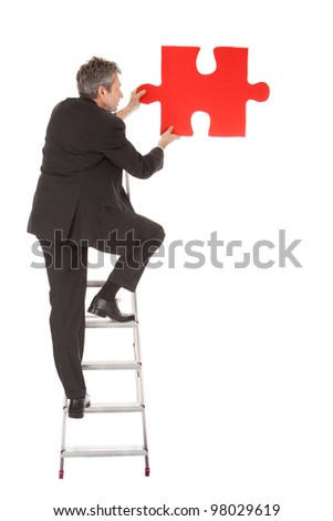 Senior businessman holding a jigsaw puzzle. Isolated in white