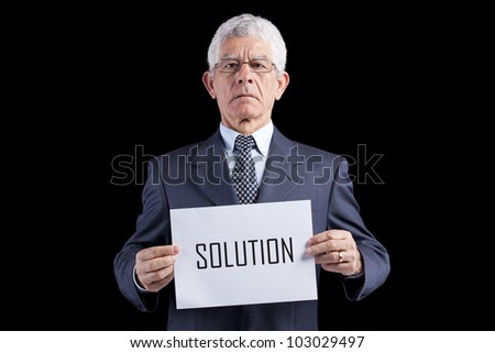 Senior businessman holding a paper with the solution word (isolated on black)