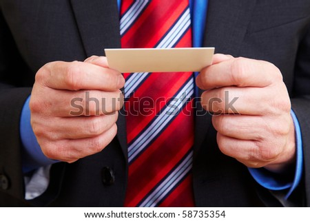 Senior businessman holding a white business card - stock photo