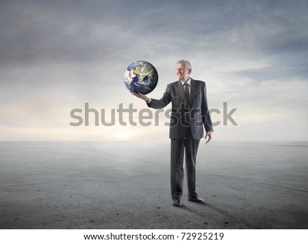 Senior businessman holding the Earth in a hand