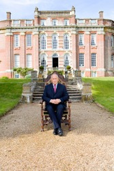 Senior businessman in a suit sitting in a chair in the garden in front of his huge manor house on a bright, sunny day