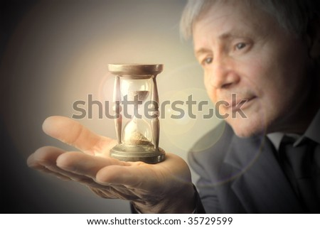senior businessman looking at hourglass