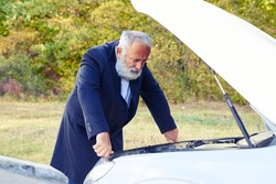 senior businessman looking under the hood of breakdown car at outdoor