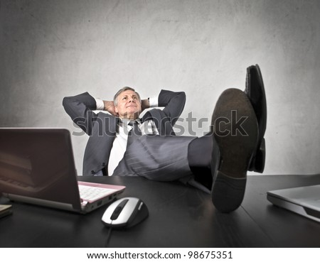 Senior businessman lying on his office chair with his feet on the desk