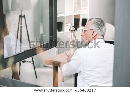 Shutterstock senior businessman near opened window at office