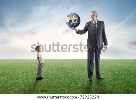 Senior businessman on a green meadow lending the Earth to a child