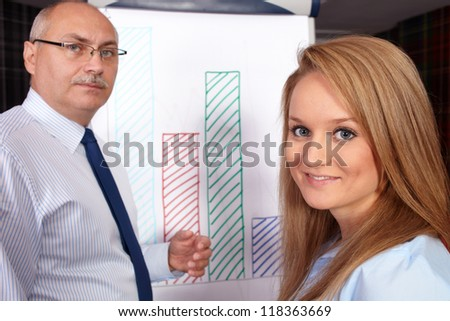 Senior businessman present graph to young attractive businesswoman, background in the office - stock photo