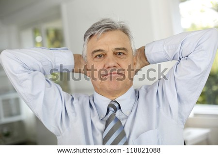 Senior businessman relaxing with arms behind head