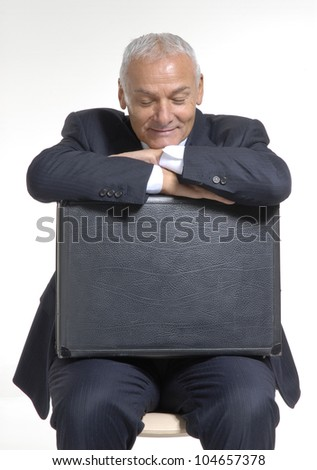 Senior businessman resting over his suitcase.