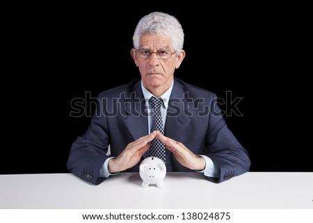 Senior businessman saving some money for his retirement (isolated on black)