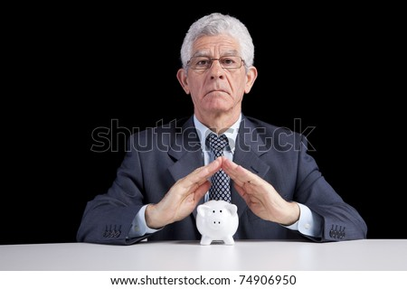 Senior businessman saving some money for his retirement (isolated on black)