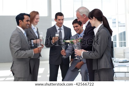 Senior businessman serving Champagne to his successful team in the office