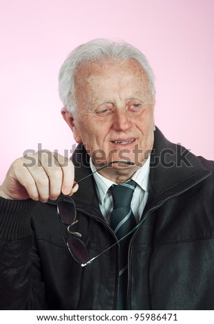Senior businessman  smiling and holding glasses in his hand