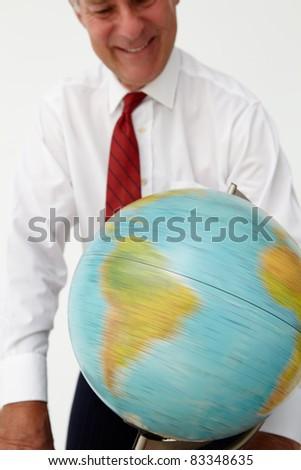 Senior businessman spinning globe