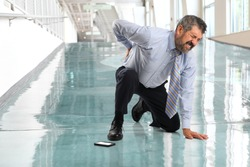 Senior businessman suffering from back injury inside office lobby