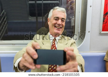 Senior Businessman Taking a Selfie in the Subway Train